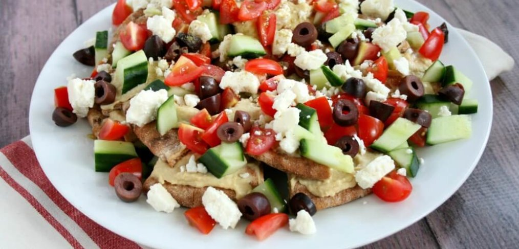 Add little Mediterranean flare to your weekly menu with No-Cook Greek Nachos. This simple vegetarian recipe packed with fresh veggies is a fresh and easy hearty appetizer, filling lunch, or light dinner.
