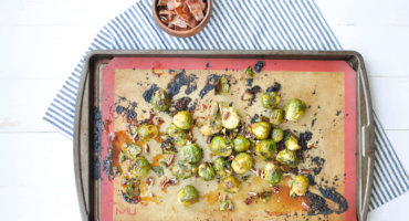 Serve an easy holiday side dish that's loaded with bright seasonal flavor, salty sweet Maple Bacon Glazed Brussels Sprouts with Toasted Pecans.
