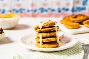 Mini Carrot Cake Pancakes with Vanilla Greek Frosting from Holley Grainger - Image of five cakes stacked on a white plate with icing drizzle