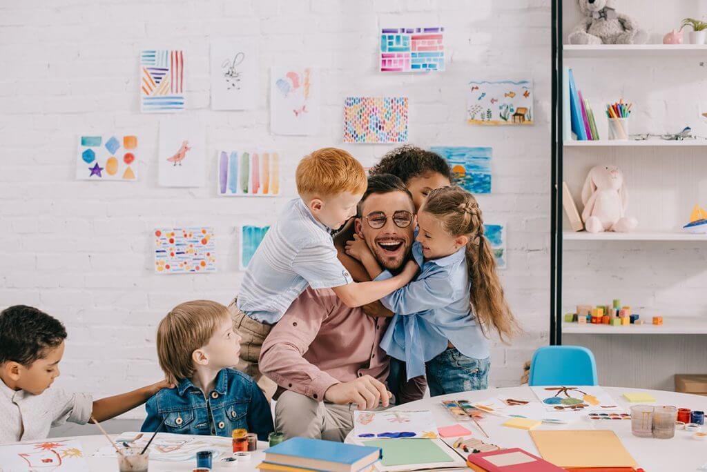 Kids hugging their classroom teacher