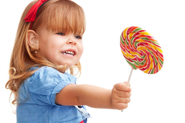 Give away leftover Halloween Candy in Halloween Buyback programs at local dentists and business - image of girl handing back lollipop