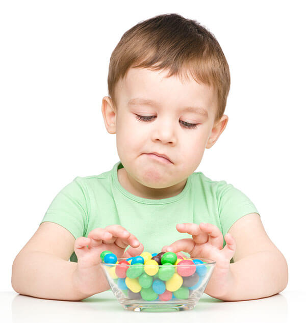 Should you allow your child to self-regulate candy intake, like this preschooler boy with bowl of M&M's?