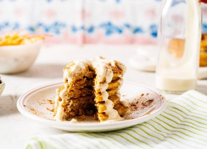 Mini Carrot Cake Pancakes with Vanilla Greek Yogurt Frosting from Holley Grainger - Image of five cakes stacked on a white plate with icing drizzle and a wedge shaped piece cut through the stack
