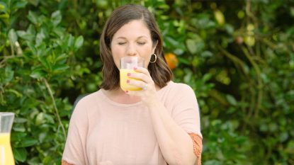 Holley Grainger Sipping Florida Orange Juice in an Orange Grove